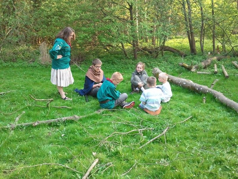 Spejderne sidder på græsset og fortæller historier